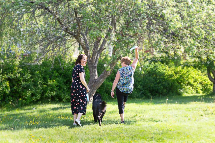 två personer och en hund går i lummig sommarmiljö